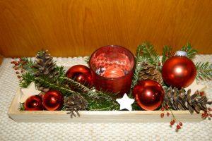 Adventsdekoration mit Holztablett, Kugeln, Windlicht, Zweigen und Zapfen