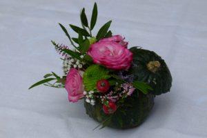 Kleiner Kürbis als Blumensteckgefäß