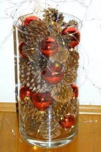 In eine Glasvase werden Kugeln und Zapfen geschichtet