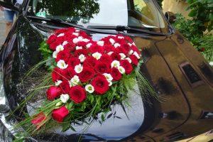 Herz mit roten Rosen und weißen Blumen auf Brautauto