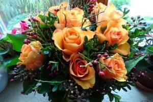 Blumenstrauß in orange mit Rosen, Efeu und Hagebutten