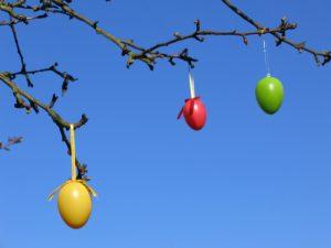 Bunte Ostereier am Baum vor blauem Himmel