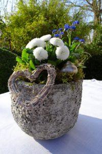 Mit Herz, Schneckenhaus und Moos geschmückter Frühlingsblumentopf