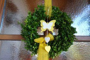 Türkranz geschmückt mit gelbem Rupfenband, Schmetterling und Herzen